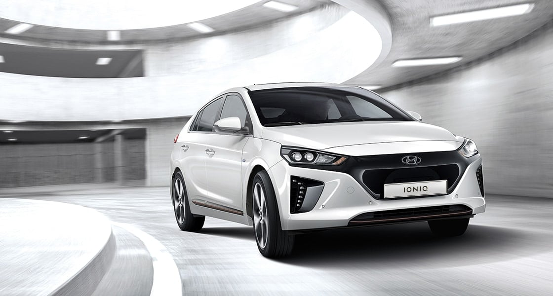 Side front view of white Ioniq electric driving in the car park tower