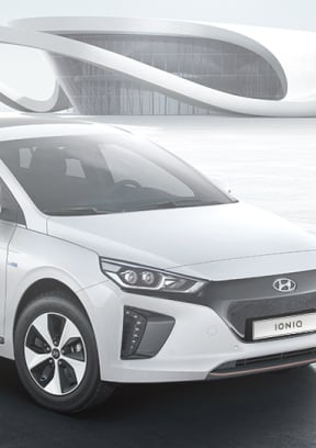 White color Ioniq Electric is placed in front of a building with unique design